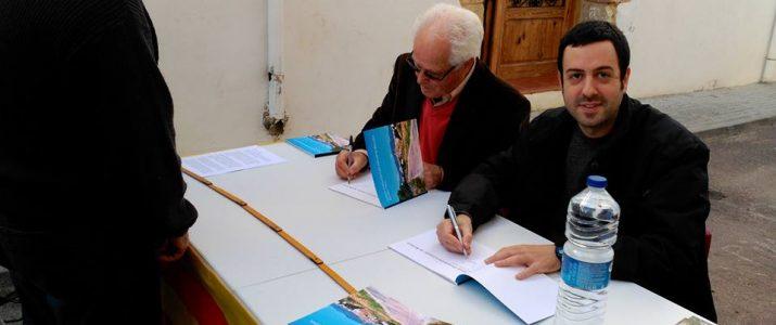 Salva Mateu, l'autor del llibre, i José Miguel García, prologuista, signen alguns exemplars lliurats als assistens a la presentació