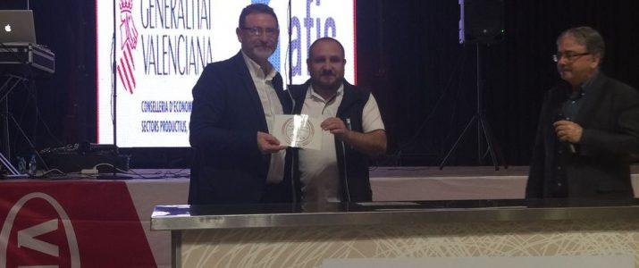 Vicent Casanova recollint el premi de la mà de Víctor Bellmunt, secretari de la IGP